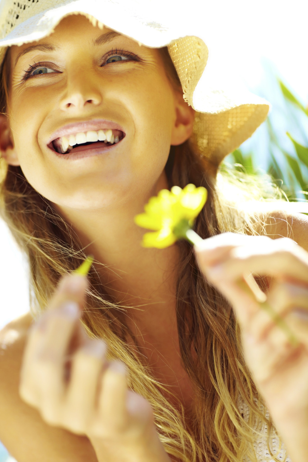 Closeup of a happy young woman with great teeth holding a yellow flower