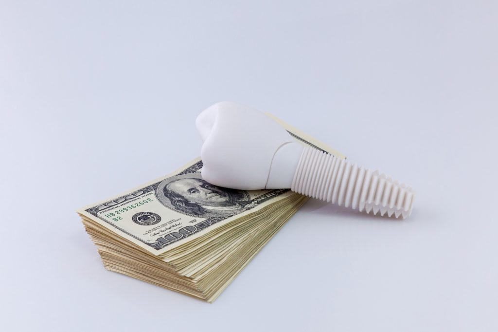 Model implant and money representing the cost of dental implants in Belmont